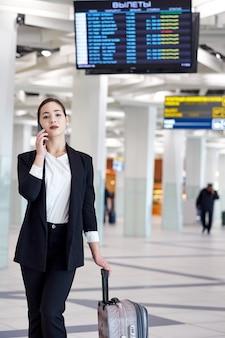 Mujer de negocios asiática joven en aeropuerto con bolsa de carro, hablando por teléfono y sonriendo.