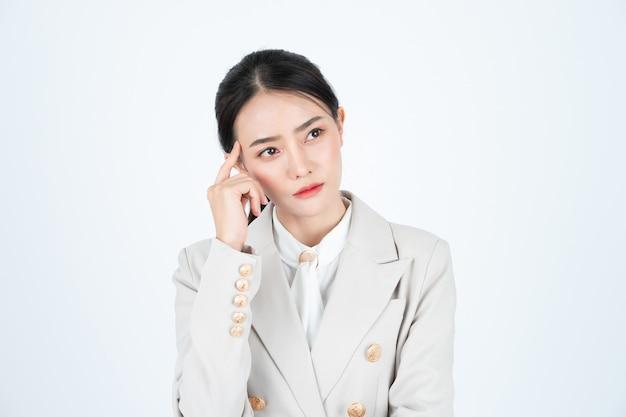 Mujer de negocios asiática joven en camisa blanca y traje beige