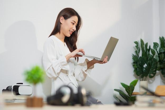 Mujer de negocios asiática joven emprendedor que trabaja en la oficina en casa con internet usando la computadora portátil, mirada femenina feliz en la pantalla de la computadora escuchar y aprender cursos en línea en el apartamento