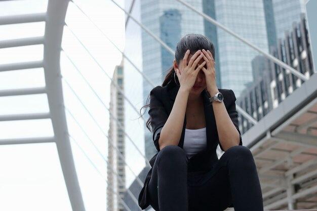 Mujer de negocios asiática joven estresada deprimida