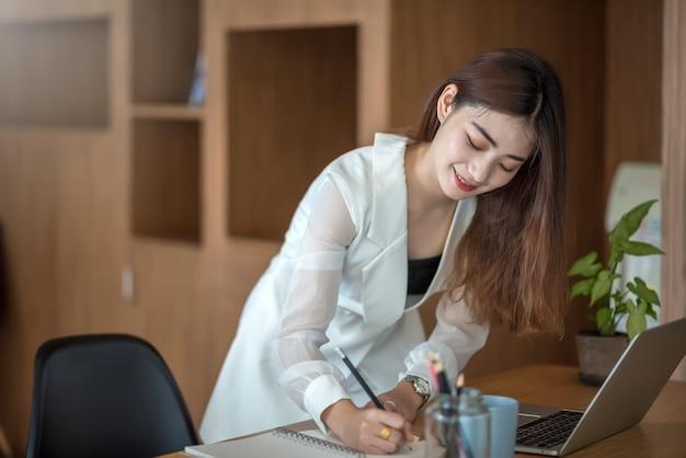 Mujer de negocios asiática joven de pie tomando notas en el cuaderno con la computadora portátil en el escritorio en la oficina