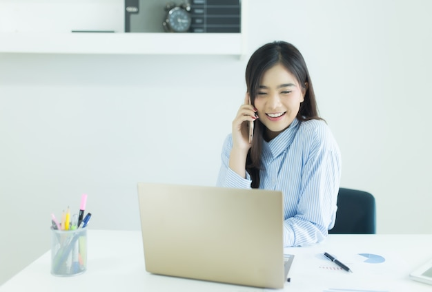 Mujer de negocios asiática joven que habla en el teléfono móvil y que sonríe en su lugar de trabajo
