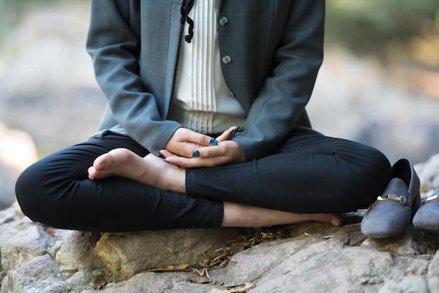 Mujer de negocios asiática joven que hace la meditación de la yoga en la roca.
