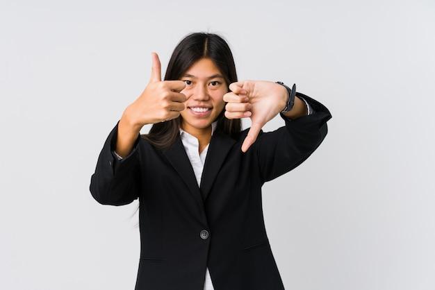Mujer de negocios asiática joven que muestra los pulgares hacia arriba y hacia abajo, difícil elegir el concepto