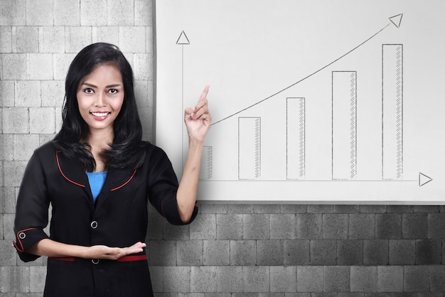 Mujer de negocios asiática joven que señala en la carta cada vez mayor