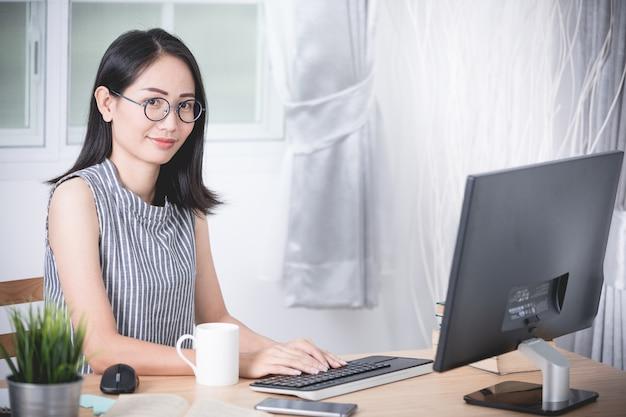 Mujer de negocios asiática joven que trabaja con la computadora