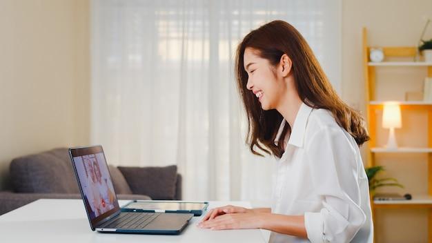 Mujer de negocios asiática joven que usa videollamada portátil hablando con papá y mamá de la familia mientras trabaja desde casa en la sala de estar. autoaislamiento, distanciamiento social, cuarentena para la prevención del coronavirus.