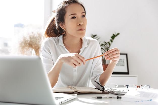 Mujer de negocios asiática pensativa mirando a otro lado mientras está sentado junto a la mesa en la oficina