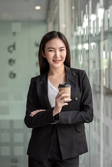 Mujer de negocios asiática de pie sosteniendo un café en una oficina moderna.