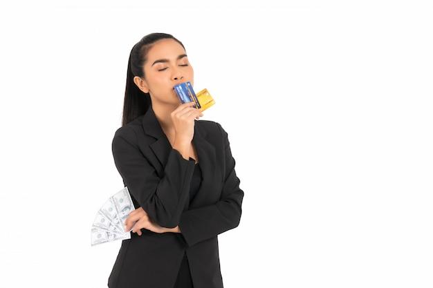 Mujer de negocios asiática que lleva un traje negro que sostiene tarjetas y el dinero de crédito