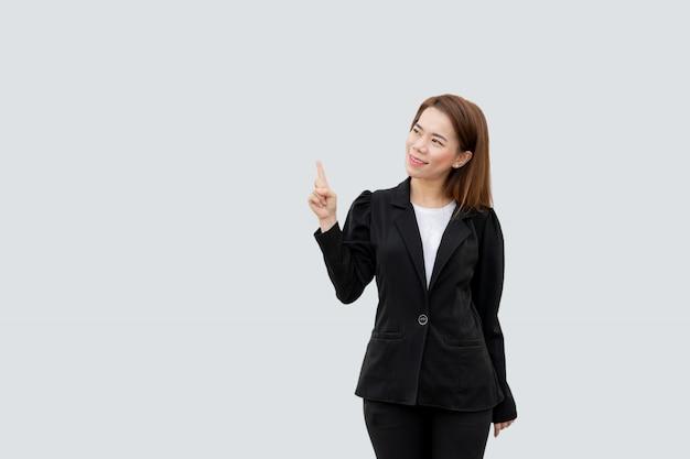 Mujer de negocios asiática que señala el dedo que presenta con el pelo largo en traje negro aislado en color blanco