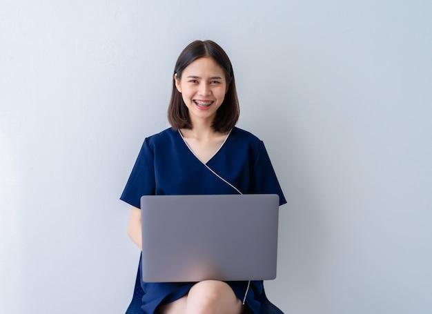 Mujer de negocios asiática que se sienta en silla y que usa la computadora portátil en hogar de la oficina.