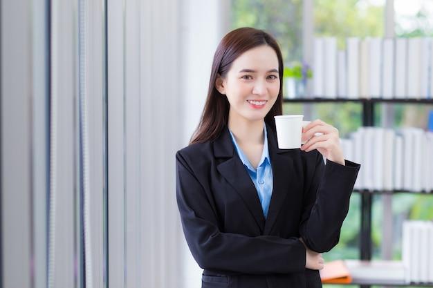 Mujer de negocios asiática que viste camisa azul y traje negro sostiene una taza de café en la mano y sonríe