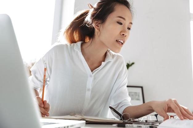 Mujer de negocios asiática sonriente concentrada leyendo documentos mientras está sentado junto a la mesa en la oficina