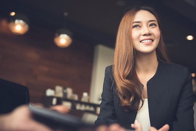 Mujer de negocios asiática sonriente que se encuentra con el cliente en café
