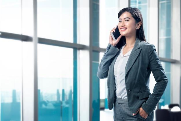 Mujer de negocios asiática sonriente que habla en su teléfono móvil