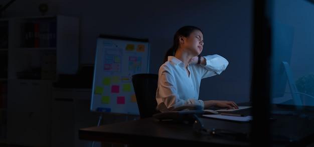 La mujer de negocios asiática tiene dolor de cuello porque usa la computadora y trabaja mucho tiempo por la noche.