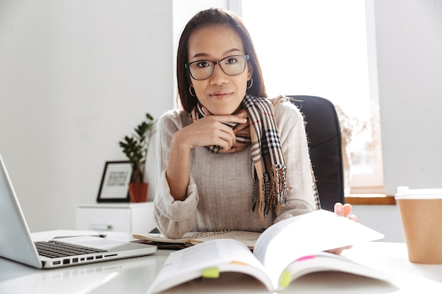 Mujer de negocios asiática tranquila complacida en anteojos mirando al frente mientras está sentado junto a la mesa en la oficina