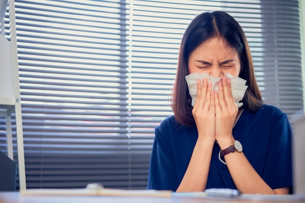 La mujer de negocios asiática utiliza una servilleta de papel la boca y la nariz porque la alergia en la mesa en la sala de la oficina.