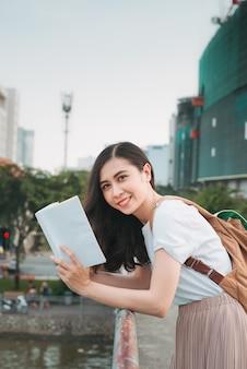 Mujer de negocios asiática viajando, de pie junto al puente de barandilla, libro de lectura sobre el fondo de la ciudad.