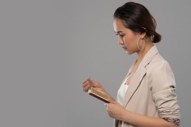 Mujer de negocios asiáticos con un peine y cabello problemático sobre fondo blanco.