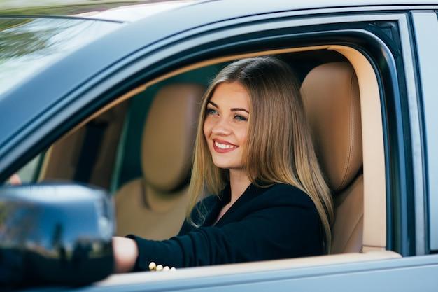 Mujer de negocios atractiva con gafas de sol sonriendo y conduciendo su coche.