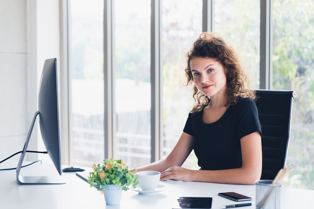 Mujer de negocios atractiva joven que sonríe mientras que se sienta en escritorio de oficina