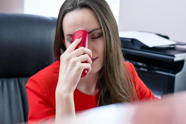Mujer de negocios atractiva de pelo oscuro en traje rojo y teléfono rojo en la mano sufriendo de dolores de cabeza. el concepto de trabajo duro en la oficina. monocromo.