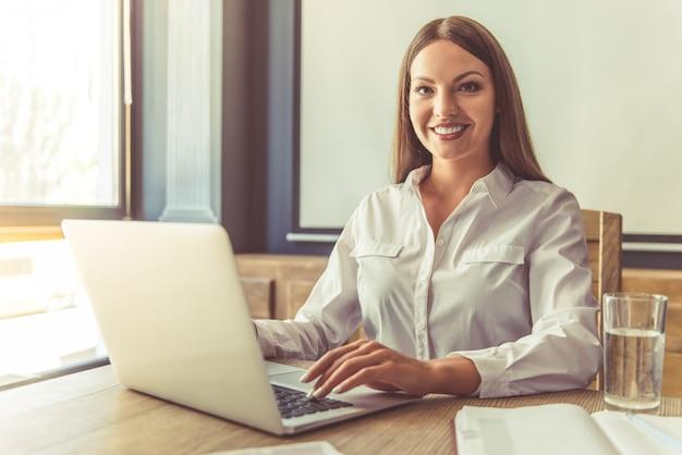 Mujer de negocios atractiva trabajando en equipo portátil