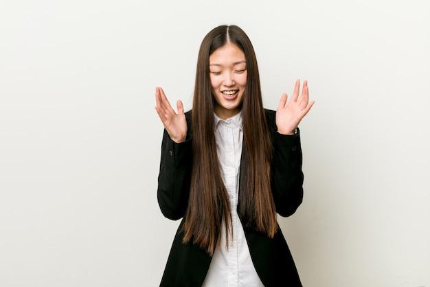 Mujer de negocios bastante china joven alegre que ríe mucho.