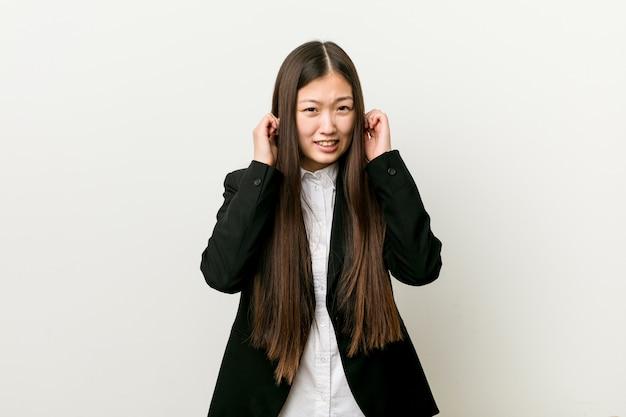 Mujer de negocios bastante china joven que cubre los oídos con las manos.