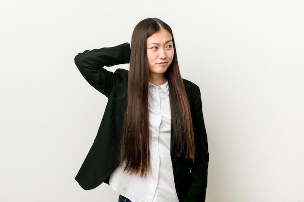 Mujer de negocios bastante china joven que toca la parte posterior de la cabeza, pensando y tomando una decisión.