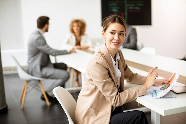 Mujer de negocios bastante joven analizando gráfico de negocios frente a su equipo en la oficina