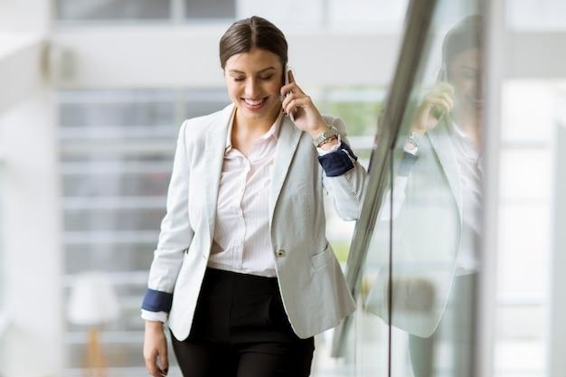 Mujer de negocios bastante joven se encuentra en las escaleras de la oficina y utiliza el teléfono móvil