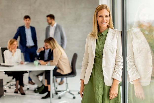 Mujer de negocios bastante joven de pie en la oficina frente a su equipo