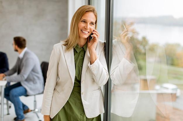 Mujer de negocios bastante joven de pie en la oficina y con teléfono móvil frente a su equipo