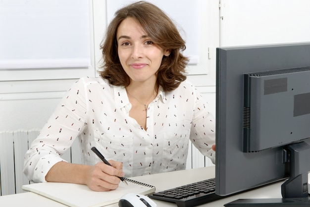 Mujer de negocios bastante joven que trabaja en la pc en la oficina