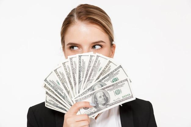 Mujer de negocios bastante rubia escondiéndose detrás del dinero y mirando a otro lado sobre la pared blanca