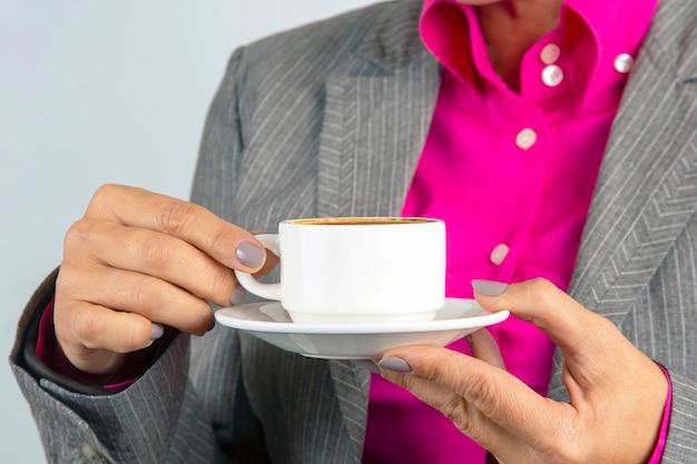 Mujer de negocios bebe café de una taza blanca de cerca