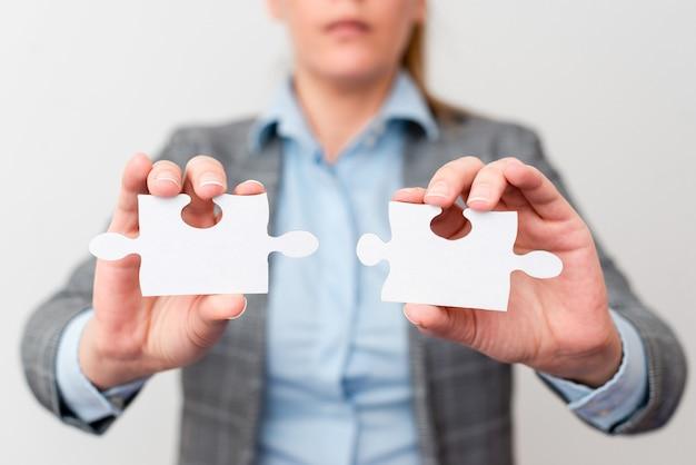 Mujer de negocios bien vestida sosteniendo dos piezas de rompecabezas, mujeres adultas profesionales resolviendo ideas faltantes, estrategia para nuevas ideas