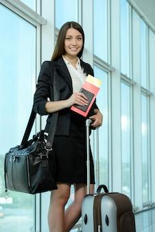 Mujer de negocios en los billetes de avión que esperan su vuelo.