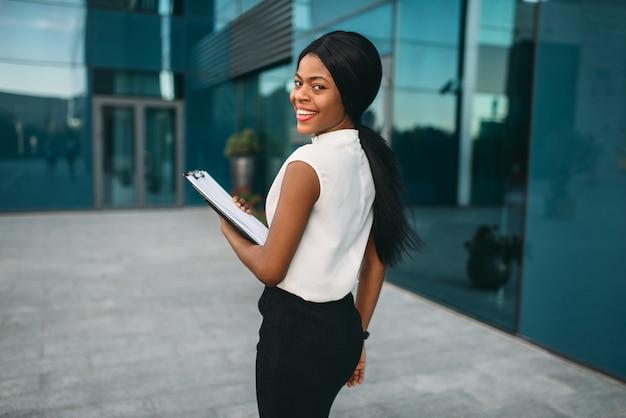 Mujer de negocios con bloc de notas al aire libre, vista posterior, edificio de oficinas en el fondo. empresaria negra en falda y blusa blanca