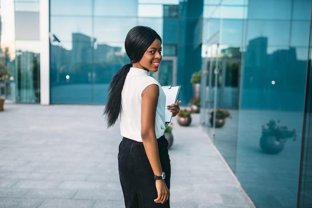 Mujer de negocios con bloc de notas al aire libre, vista posterior