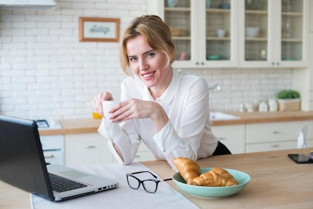 Mujer de negocios bonita con café usando la computadora portátil