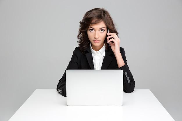 Mujer de negocios bonita confiada concentrada que trabaja con la computadora portátil y que habla por teléfono celular