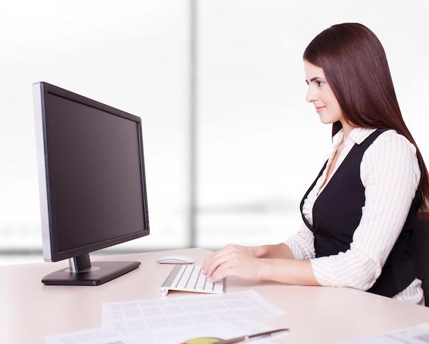Mujer de negocios bonita en el escritorio de oficina