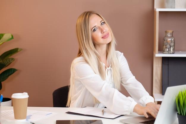 Mujer de negocios bonita joven con el cuaderno en la oficina