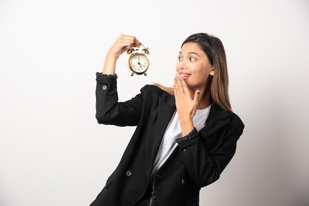 Mujer de negocios en busca de un reloj de alarma en la pared blanca.