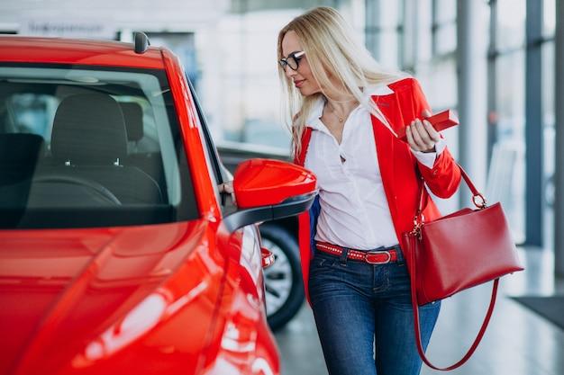 Mujer de negocios buscando un auto móvil en una sala de exposición de automóviles Foto gratis