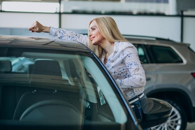 Mujer de negocios buscando un auto móvil en una sala de exposición de automóviles